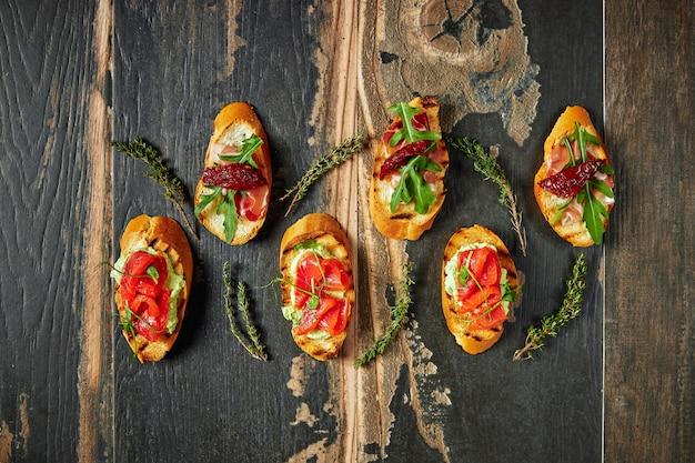 Bruschetta tradicional com presunto e presunto secos de parma. antepasto italiano conjunto sanduíches em uma placa de madeira rústica vista superior