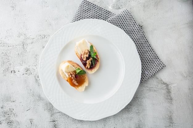Bruschettas com legumes. comece pratos com tomate cereja, cream cheese. deliciosos petiscos com chouriço e tomates assados. composição de alimentos, saborosa refeição italiana. pão com queijo