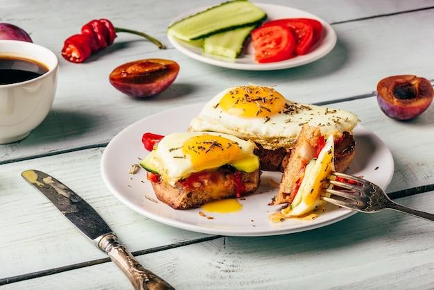 Bruschettas com legumes e ovo frito na chapa branca, xícara de café e algumas frutas sobre madeira