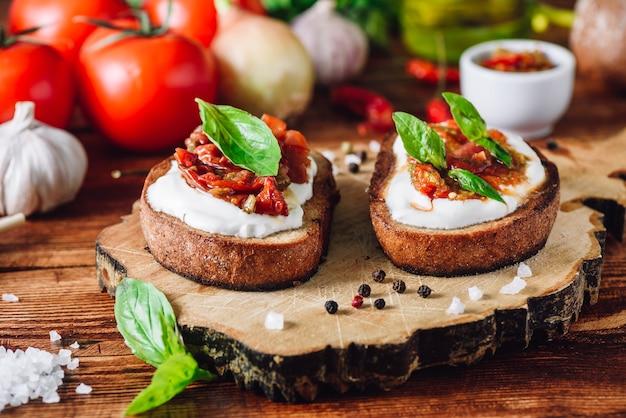Bruschettas com tomate seco e molho picante na tábua de cortar