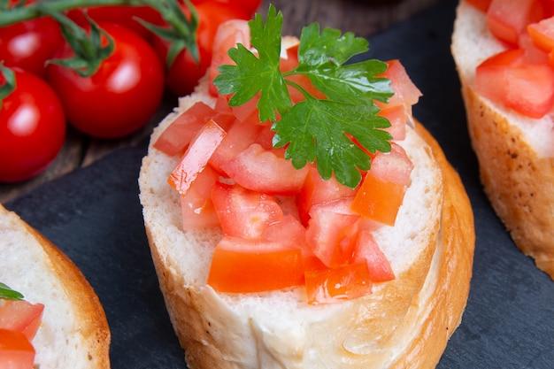 Bruschettas italianas tradicionais com tomate cereja na placa de pedra