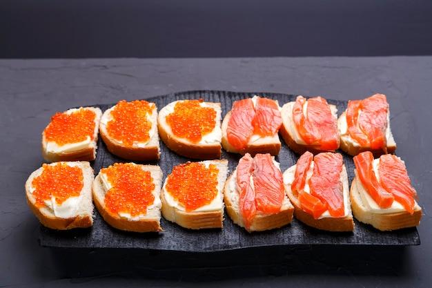 Bruschettes com caviar de manteiga vermelha e truta em uma placa de madeira preta sobre um fundo cinza. foto horizontal
