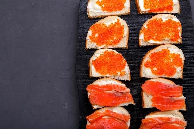 Bruschettes com caviar vermelho manteiga e truta dispostos em um quadro negro em um espaço de cópia de fundo de concreto cinza. foto vertical