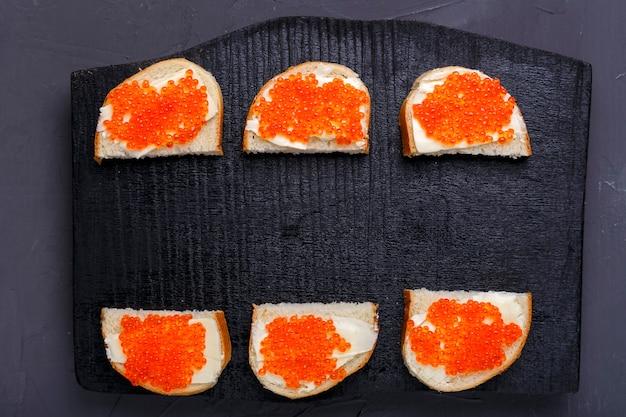 Bruschettes com manteiga e caviar vermelho dispostos em uma placa preta em um espaço de cópia de fundo de concreto cinza. foto horizontal