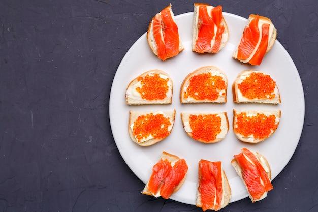 Bruschettes com manteiga e caviar vermelho e salmão em um prato branco em um espaço de cópia de fundo de concreto cinza. foto horizontal