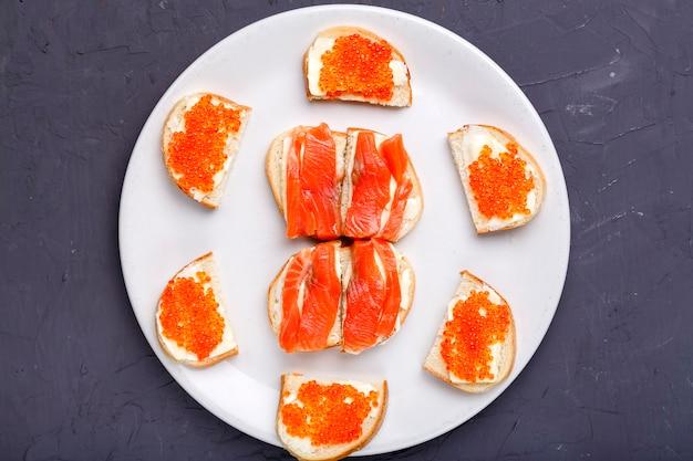 Bruschettes com manteiga e caviar vermelho e salmão em um prato branco sobre um fundo cinza de concreto. foto horizontal