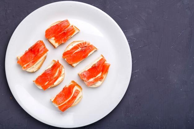 Bruschettes com manteiga e salmão em um prato branco sobre um fundo cinza de concreto. copie o espaço. foto horizontal