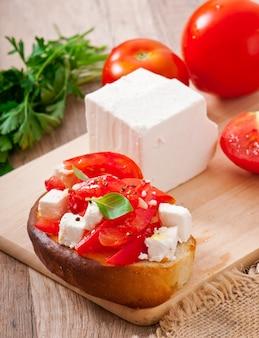 Brusqueta com tomate, queijo feta e manjericão