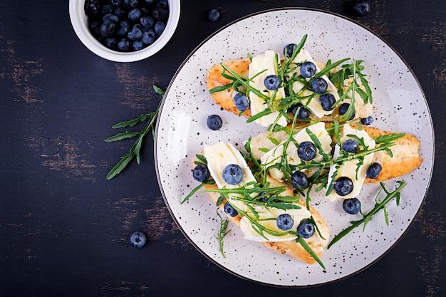 Brusqueta. torradas crostini com frutas frescas mirtilo e mel, queijo brie, rúcula. vista do topo, .