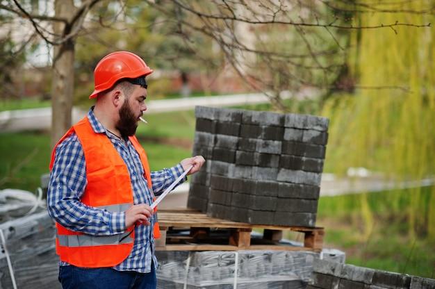 Brutal barba fumar trabalhador homem terno trabalhador da construção civil no capacete de segurança laranja contra pavimento com uma fita métrica na mão.