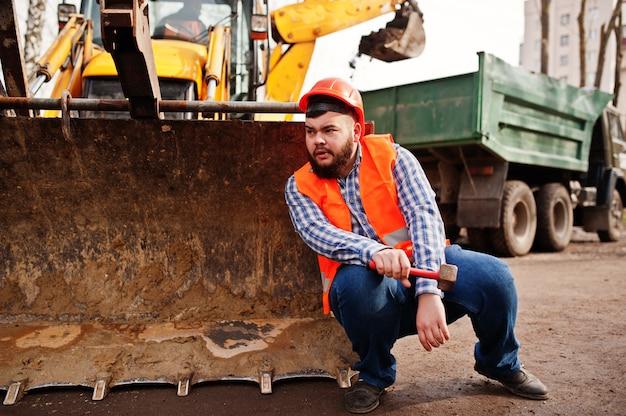Brutal barba trabalhador homem terno trabalhador da construção civil no capacete de segurança laranja, contra traktor com martelo na mão.