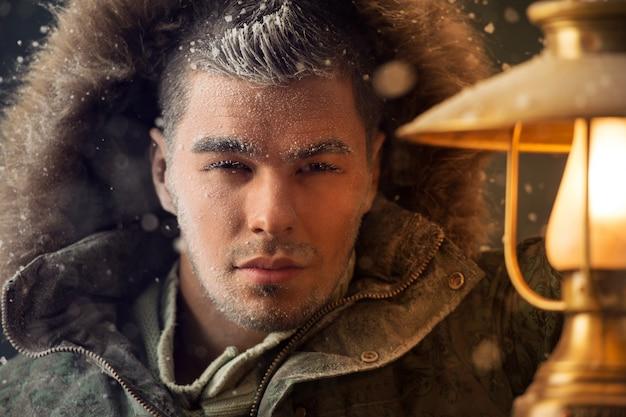 Brutal homem caminhando sob tempestade de neve à noite iluminando seu caminho com a lanterna