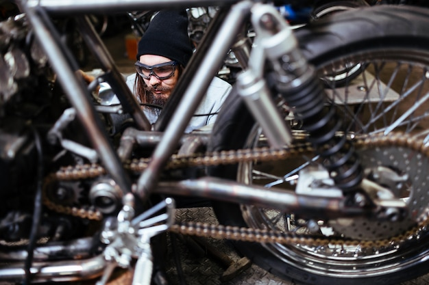 Brutal tattooed biker personalizando motocicleta