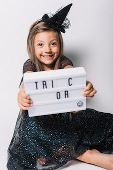 Bruxa alegre, mostrando a placa com a escrita