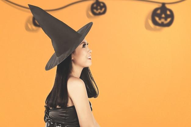 Bruxa asiática com um chapéu em pé e um fundo colorido