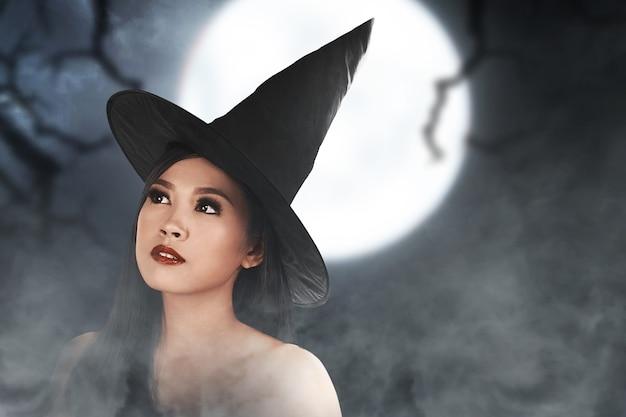 Bruxa asiática com uma capa em pé com a cena noturna de fundo