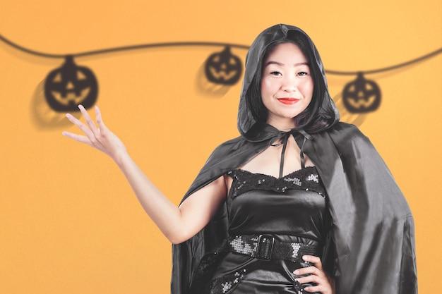Bruxa asiática com uma capa em pé e um fundo colorido