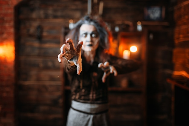 Bruxa assustadora com as mãos estendidas, vista frontal, sessão espiritual. a adivinhadora chama os espíritos, terrível cartomante