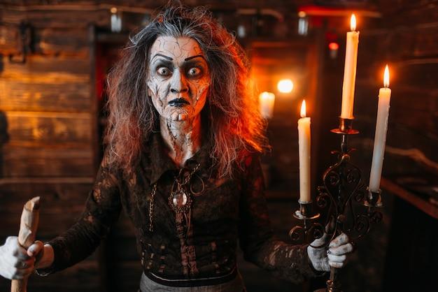 Bruxa assustadora com castiçal e bengala lê o feitiço