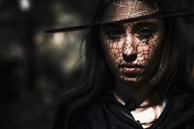 Bruxa assustadora com sombra web no rosto