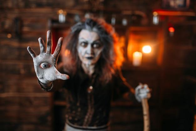 Bruxa assustadora com um olho na palma da mão lê feitiço místico, sessão espiritual. a adivinhadora chama os espíritos, terrível cartomante