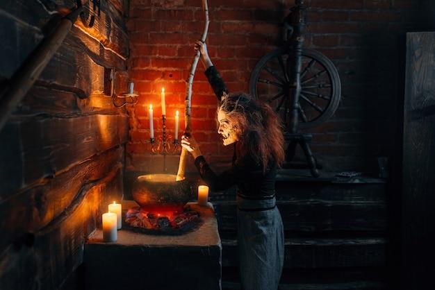 Bruxa assustadora cozinhando sopa e feitiço de leitura, poderes sombrios da bruxaria, sessão espiritual com velas.