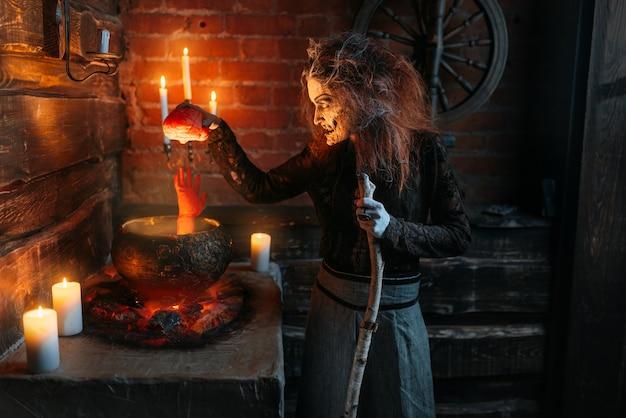 Bruxa assustadora lê feitiço sobre a panela com partes do corpo humano, poderes sombrios de bruxaria, sessão espiritual com velas.