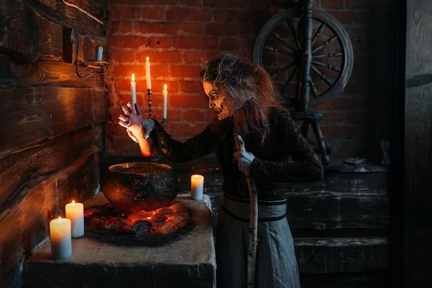 Bruxa assustadora lê feitiço sobre a panela, poderes sombrios da bruxaria, sessão espiritual com velas. predicadora feminina chama os espíritos, terrível futura contadora
