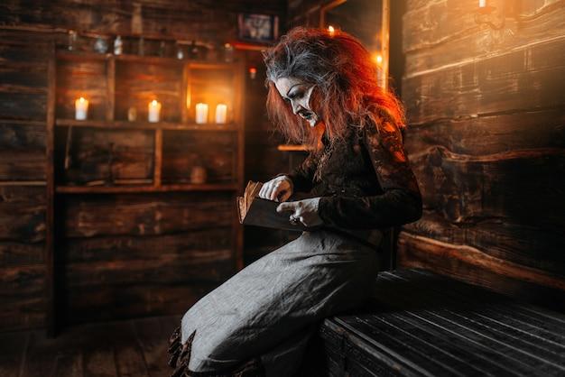 Bruxa assustadora lê livro de feitiços, poderes das trevas da bruxaria, sessão espiritual.