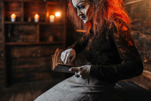 Bruxa assustadora lê livro de feitiços, sessão espiritual