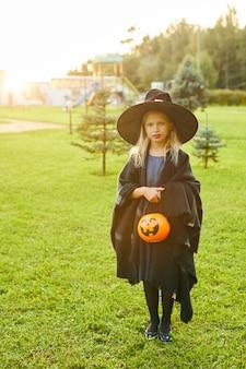 Bruxa bonita segurando balde de doces ou travessuras