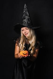 Bruxa bonito segurando o brinquedo jack-o-lanterna