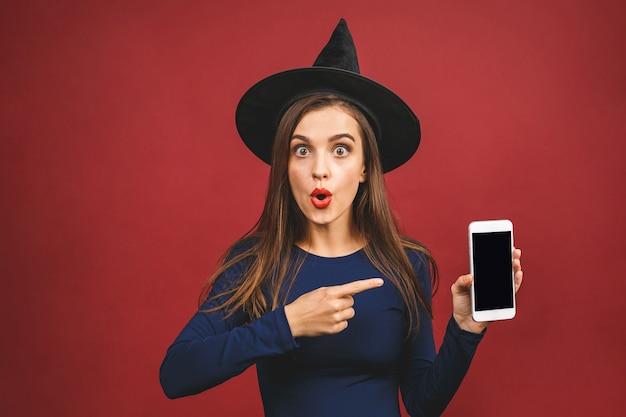 Bruxa de halloween com a tela do telefone móvel - isolada sobre fundo vermelho. jovem emocional em traje de halloween. festa de halloween.