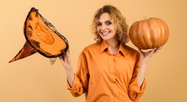 Bruxa de halloween com abóbora a sorrir. garota feliz com chapéu de bruxas mágicas. doçura ou travessura. hora do halloween.