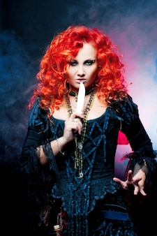 Bruxa de halloween cria mágica. mulher com cabelo vermelho em traje de bruxas