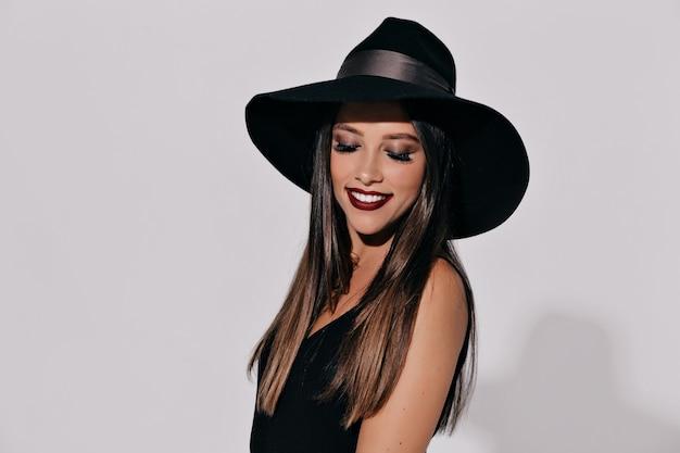 Bruxa de halloween posando na parede isolada. bela jovem eficaz de bruxas chapéu e fantasia segurando a abóbora. projeto amplo de arte para festa de halloween