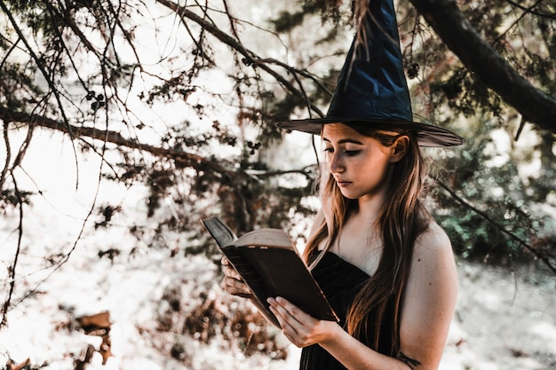 Bruxa de halloween segurando antigo tomo na floresta ensolarada