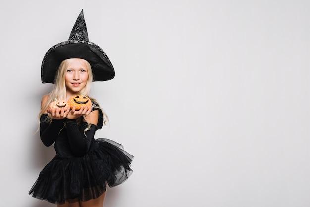 Bruxa doce mostrando jack-o-lanternas