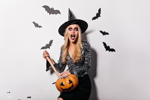 Bruxa elegante com grande chapéu segurando abóbora e gritando. adorável vampiro loiro posando com estaca de álamo tremedor.