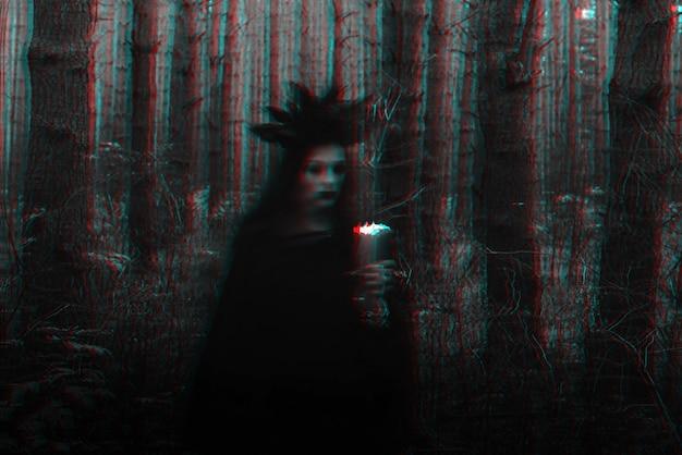 Bruxa em uma fantasia preta realiza feitiços sombrios com velas na floresta. foto desfocada com desfoque devido ao longo tempo de exposição. preto e branco com efeito de realidade virtual de falha 3d