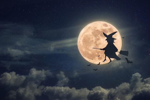 Bruxa em uma vassoura com morcegos voando à noite em um fundo de lua cheia