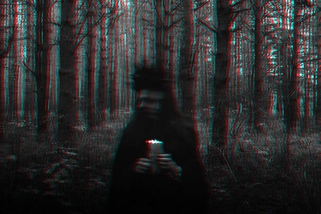 Bruxa fantasiada realiza feitiços sombrios com velas na floresta. foto desfocada com desfoque devido ao longo tempo de exposição. preto e branco com efeito de realidade virtual de falha 3d