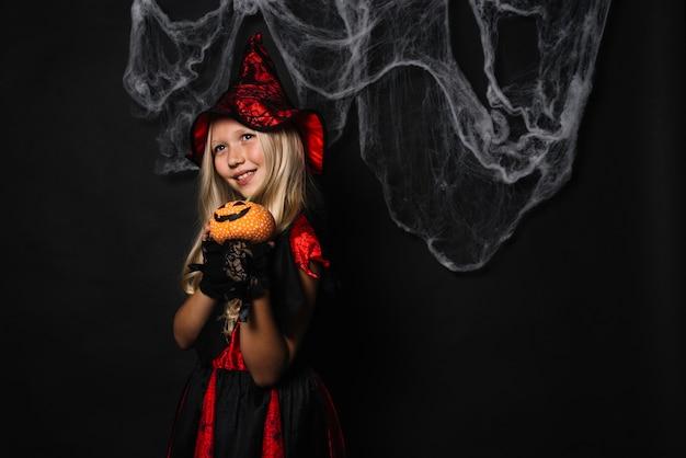 Bruxa fofa com jack-o-lanterna