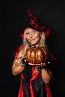 Bruxa fofa mostrando a abóbora