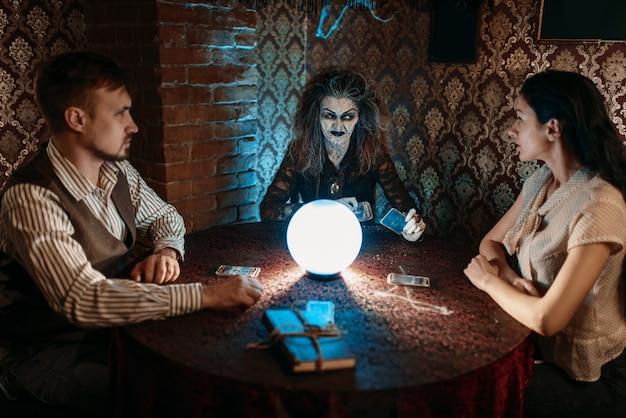 Bruxa, homem e mulher em sessão espiritual
