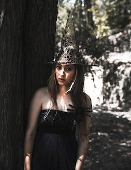 Bruxa impressionante com aranha assustador na floresta ensolarada