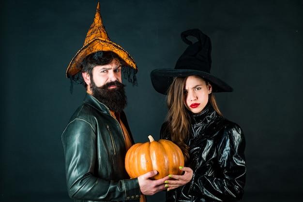 Bruxa jovem com chapéu de halloween e homem barbudo sobre fundo preto. projeto de halloween para o espaço da cópia. homem bonito e mulher vestindo roupas de halloween.