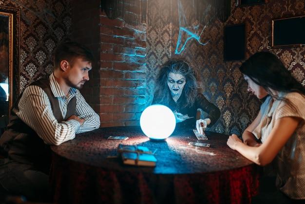 Bruxa lê um feitiço sobre uma bola de cristal, jovem casal em sessão espiritual.