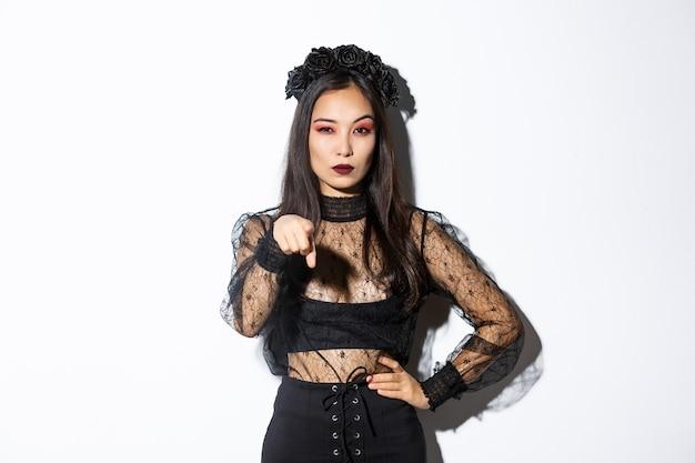 Bruxa malvada asiática arrogante e atrevida, mulher com fantasia de halloween, apontando o dedo para você e parecendo misteriosa, de pé sobre um fundo branco.