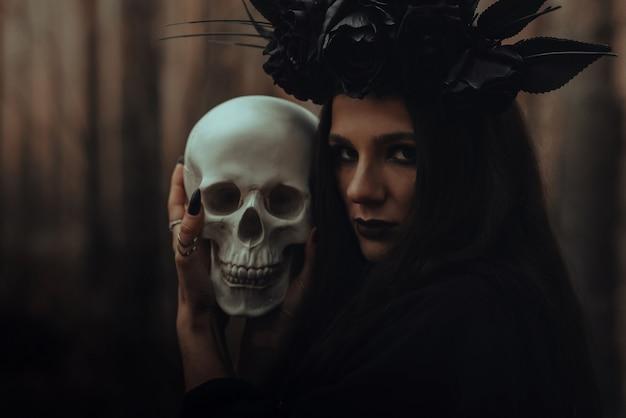 Bruxa malvada assustadora em trapos pretos segura o crânio de um homem morto em um ritual sombrio na floresta